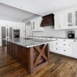 Trendy kitchen with wood island and white outer cabinets.